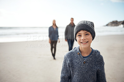 Buy stock photo Cropped portrait of a happy young boy spending the day on the beach with his parents