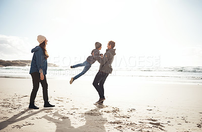 Buy stock photo Full length shot of a happy young couple spending the day with their son on the beach