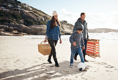 Buy stock photo Full length shot of a happy young family walking along the beach for a picnic during a day out
