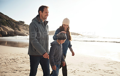 Buy stock photo Cropped shot of a happy young family walking along the beach together during a day out