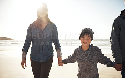 Buy stock photo Cropped portrait of a happy young boy walking and holding his parents' hands during a day out on the beach
