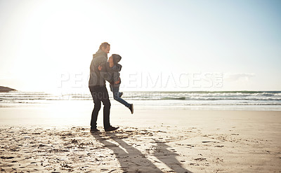Buy stock photo Full length shot of a handsome young man feeling playful while enjoying a day on the beach with his son