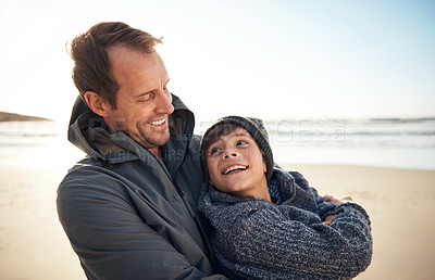 Buy stock photo Cropped shot of a handsome young man hugging his son while bonding with him on the beach
