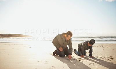 Buy stock photo Full length shot of a handsome young man and his son kneeling and writing in the sand on the beach