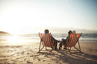 Buy stock photo Full length shot of an unrecognizable family sitting on sun loungers during an enjoyable day out on the beach together