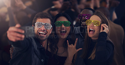 Buy stock photo Cropped shot of a group of young friends taking selfies while dancing together in a nightclub