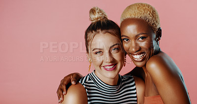 Buy stock photo Studio portrait of two beautiful young women smiling while standing against a pink background