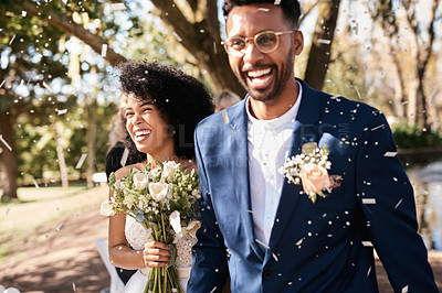 Buy stock photo Shot of a happy newlywed young couple getting showered with confetti outdoors on their wedding day