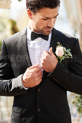 Buy stock photo Shot of a handsome young man fixing himself up and getting ready outdoors on his wedding day