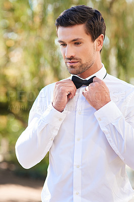 Buy stock photo Shot of a handsome young bridegroom putting on a bowtie while standing outdoors on his wedding day