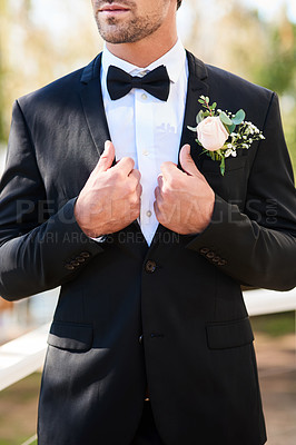 Buy stock photo Cropped shot of an unrecognizable young bridegroom adjusting his suit and getting ready outdoors on his wedding day