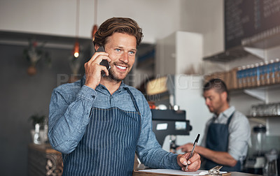 Buy stock photo Shot of a young man talking on a cellphone while working in a cafe with his colleague in the background