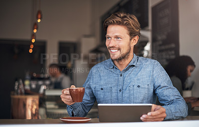 Buy stock photo Shot of a young man using a digital tablet while having coffee in a cafe