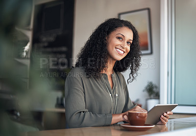 Buy stock photo Shot of a young woman using a digital tablet while having coffee in a cafe