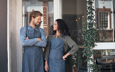 Buy stock photo Shot of two coffee shop employees standing outside their cafe