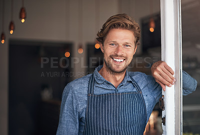 Buy stock photo Portrait of a young man standing at the doorway of his cafe