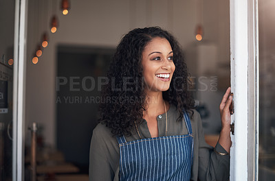 Buy stock photo Shot of a young woman standing at the doorway of her cafe