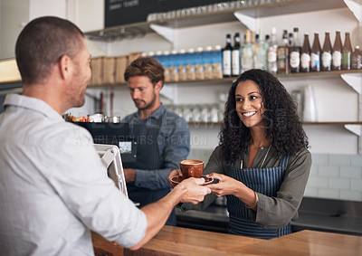 Buy stock photo Shot of a waitress serving a cup of coffee to a customer in a cafe