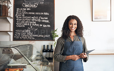 Buy stock photo Portrait of a young woman using a digital tablet while working in a cafe