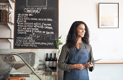 Buy stock photo Shot of a young woman using a digital tablet while working in a cafe