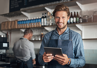 Buy stock photo Portrait of a young man using a digital tablet while working in a cafe
