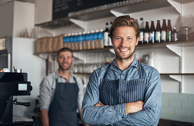 Buy stock photo Portrait of a young man working in a cafe with his colleague in the background