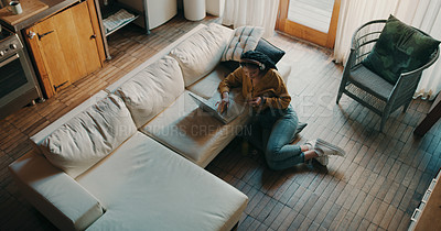 Buy stock photo High angle shot of a young woman using her credit card and laptop to shop online while relaxing at home