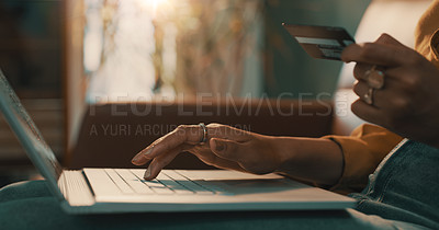 Buy stock photo Shot of an unrecognizable woman using her credit card and laptop to shop online while relaxing at home