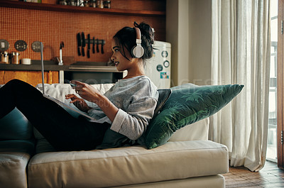 Buy stock photo Shot of an attractive young woman listening to music and using her credit card to shop online at home
