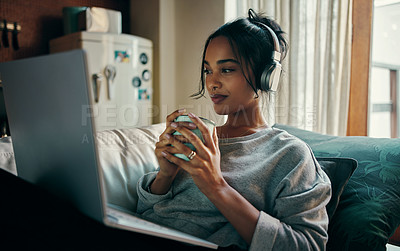 Buy stock photo Shot of an attractive young woman drinking coffee and using her laptop while relaxing at home