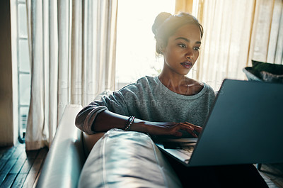 Buy stock photo Shot of an attractive young woman using her laptop while relaxing on a sofa at home