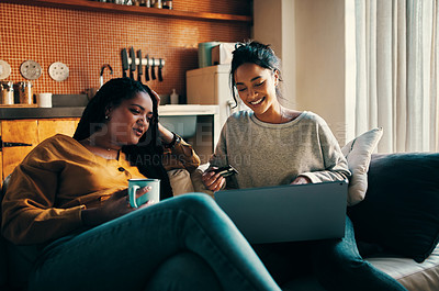 Buy stock photo Shot of two attractive young women using a credit card and laptop to shop online while relaxing together at home