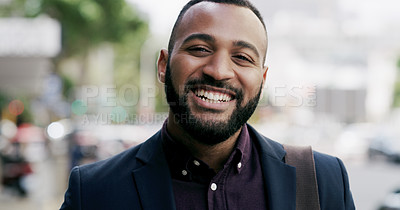 Buy stock photo Cropped portrait of a handsome young businessman smiling while standing in the city during the day