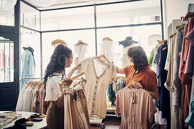 Buy stock photo Cropped shot of two young women out shopping in a clothing store