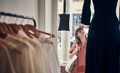 Buy stock photo Shot of a woman looking at a dress on display in the window of a clothing store