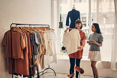 Buy stock photo Shot of a shop assistant using a digital tablet while assisting a customer in a boutique