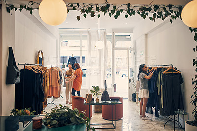 Buy stock photo Shot of young women browsing in a clothing store