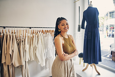 Buy stock photo Cropped shot of a young business owner standing with her arms crossed in her clothing store