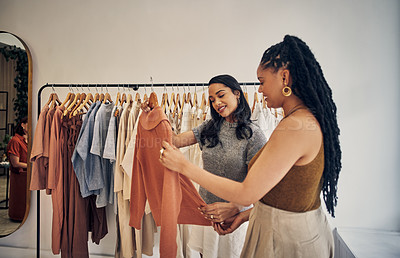 Buy stock photo Shot of two young women browsing in a clothing store