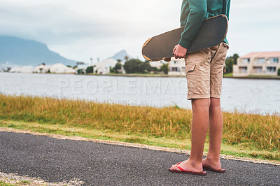 Buy stock photo Cropped shot of an unrecognizable boy standing outside alone and holding his skateboard while looking out at the lake