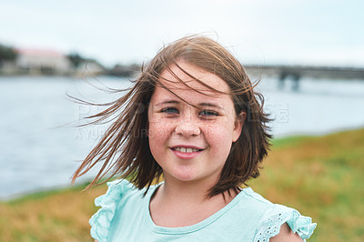Buy stock photo Cropped portrait of a happy young girl standing alone outdoors and smiling at the camera