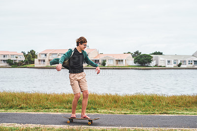Buy stock photo Full length shot of a happy young boy skateboarding alongside the lagoon during a day out alone