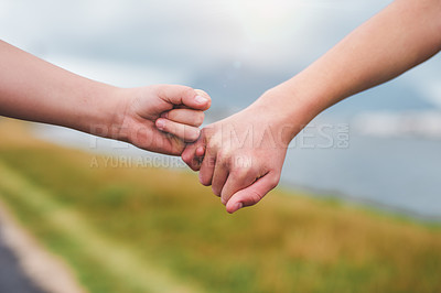 Buy stock photo Cropped shot of two unrecognizable children standing together and holding each others pinky fingers during a day out