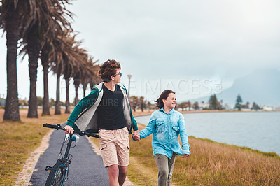Buy stock photo Cropped shot of two young children holding hands and walking alongside the lagoon together while pushing a bicycle