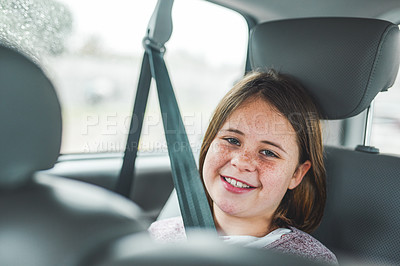 Buy stock photo Cropped portrait of a happy young girl sitting in the car and smiling during a rainstorm