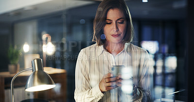 Buy stock photo Cropped shot of an attractive young businesswoman using a smartphone while working late in a modern office