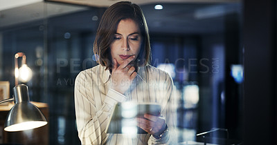 Buy stock photo Cropped shot of an attractive young businesswoman looking thoughtful while  using a digital tablet in a modern office at night