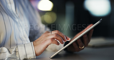Buy stock photo Cropped shot of an unrecognizable businesswoman using a digital tablet while working late in a modern office