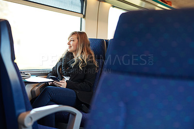 Buy stock photo Cropped shot of an attractive young woman sitting alone on a train and looking out the window during her commute