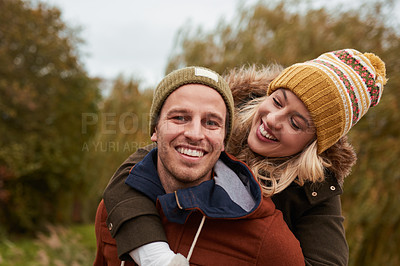 Buy stock photo Cropped portrait of an affectionate young man smiling while piggybacking his girlfriend in a park in late autumn